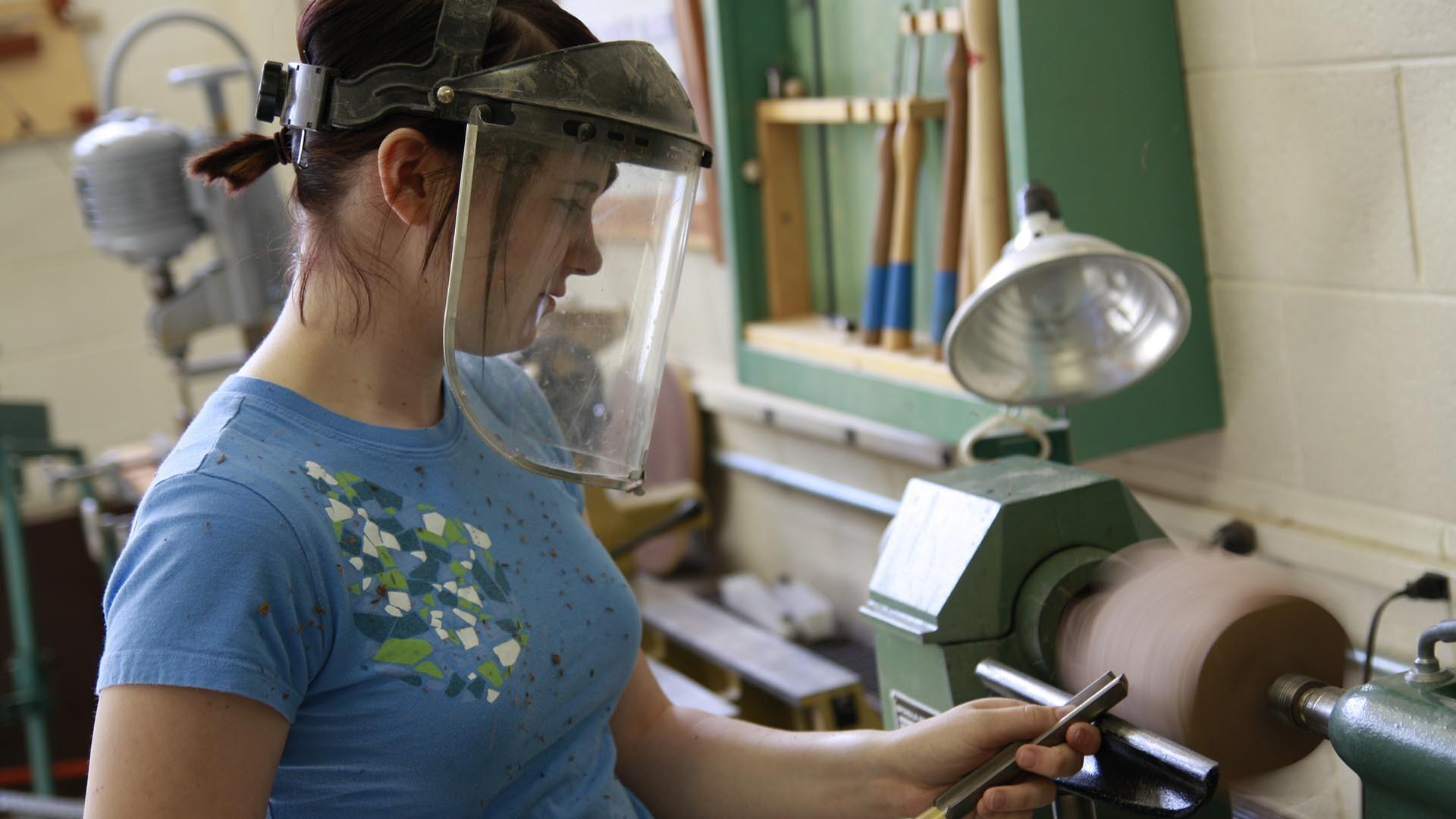 A female student using a wood working machine