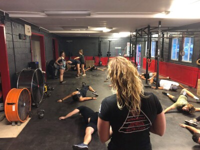 Hannah Howells at the CrossFit gym in Kahuku with other people working out it the background.